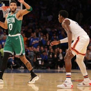 Boston Celtics forward Jayson Tatum (0) controls the ball against \New York Knicks guard RJ Barrett (9) during the first overtime at Madison Square Garden.