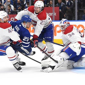 Toronto Maple Leafs forward Ondrej Kase (25) is knocked down by Montreal Canadiens defenseman Alexander Romanov (27) and forward Joel Armia (40) in front of goalie Jake Allen (34) in the second period at Scotiabank Arena.