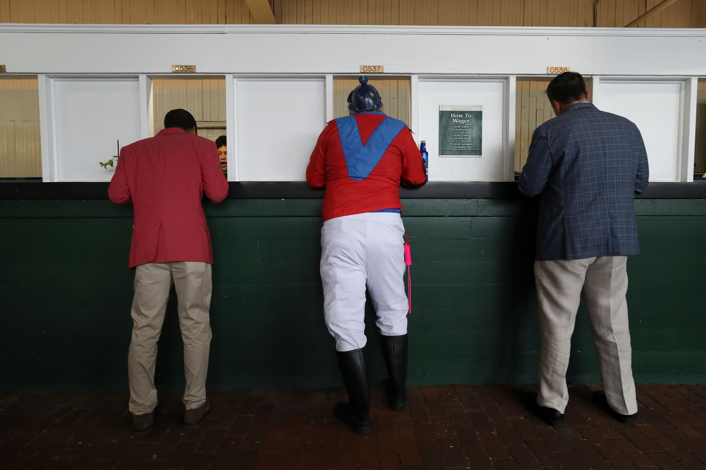 Michael Freeze, center, is not a real jockey, but that didn't stop him from dressing the part and placing a bet ahead of the Kentucky Derby at Churchill Downs on May 4, 2019