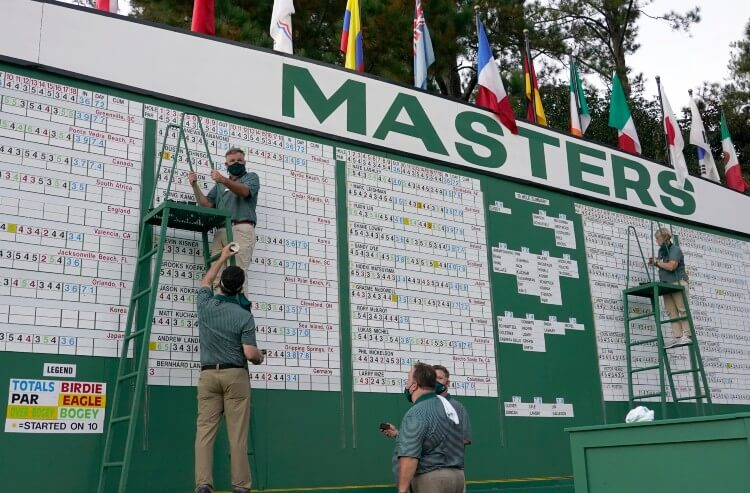 Scoreboard workers adjust the 2020 Masters leaderboard as the cut line approaches.