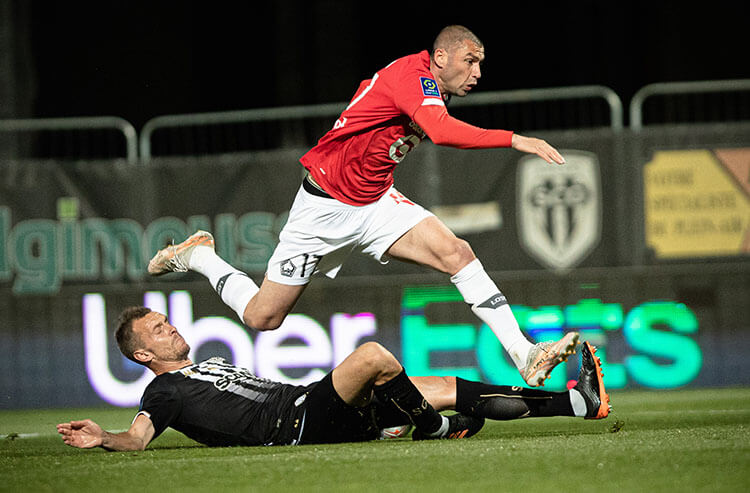 Burak Yilmaz (Top) competes during a French Ligue 1 football match between Lille and Angers at Raymond Kopa stadium in Angers, France, on May 23, 2021.